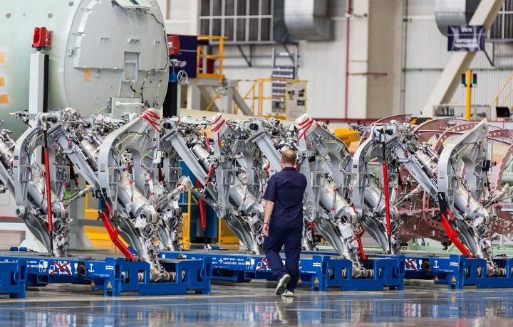 Man in front of manufacturing line for aeroplanes